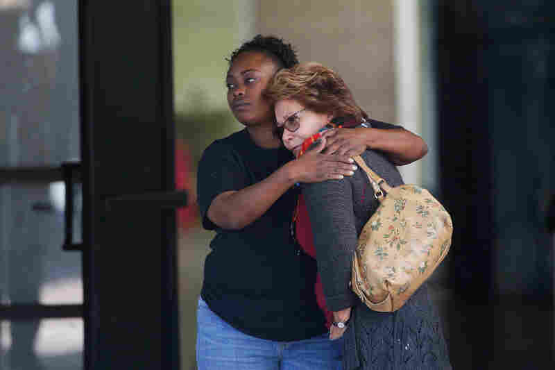 Two women embrace at a community center where family members gathered to pick up survivors after the shooting.