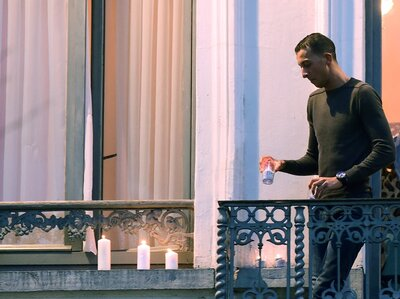 Mohamed Abdeslam places candles on a window ledge of his family's apartment Nov. 18 during a candlelight vigil in Brussels' Molenbeek district town square. Two of his brothers were among the attackers in Paris on Nov. 13. (Emmanuel Dunand/AFP/Getty Images)