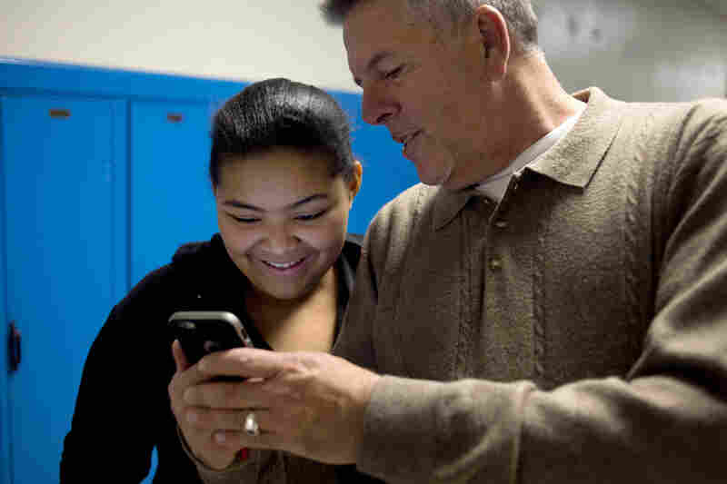 John Vowell (right) shows Tiasa Cantrell, 13, photos on his phone. Cantrell comes to Major Chords for Minors to hang out with John and Katrina while her twin sister takes guitar lessons.