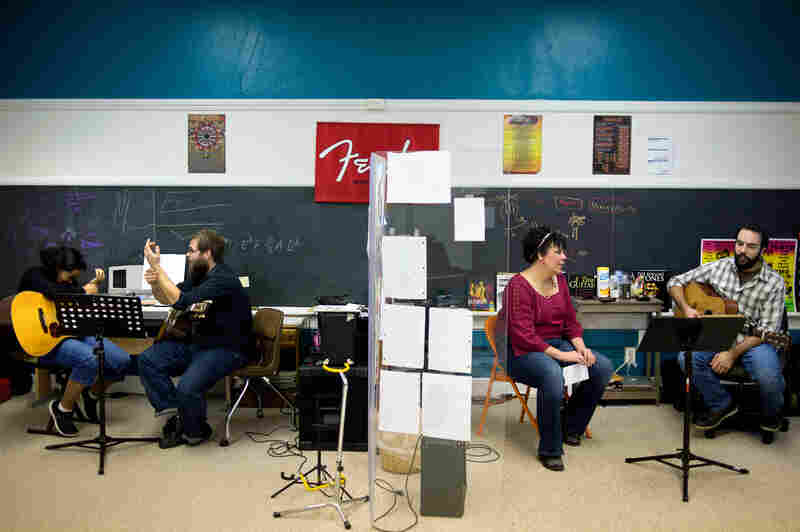 Tanzania Cantrell (from left), 13, and her guitar teacher, Ryan Fitzgerald, talk about wrist cramps while Katrina Vowell talks to guitar instructor Mike Tesch before one of his lessons begins.