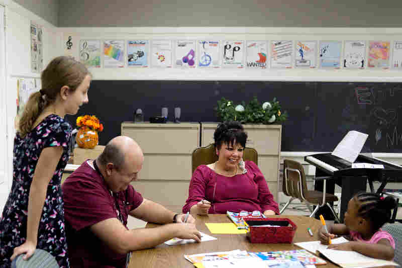 Erikka Wilkins (left), 12, waits for her father, Carl Wilkins (seated), before heading home, as Katrina Vowell (center) jokes with Joyous Austin, 5.