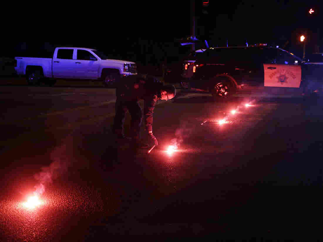 A police officer lights up flares near the scene of a shootout in San Bernardino, Calif., on Wednesday. Police say Syed Farook, 28, and Tashfeen Malik, 27, opened fire on an office holiday party in the Inland Regional Center.