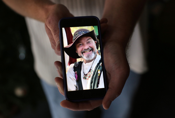 Ryan Reyes, 32, holds a photograph of his boyfriend of three years, Larry Kaufman, who was confirmed as one of the 14 people killed at the Inland Regional Center on Wednesday. The image was taken at a renaissance festival.