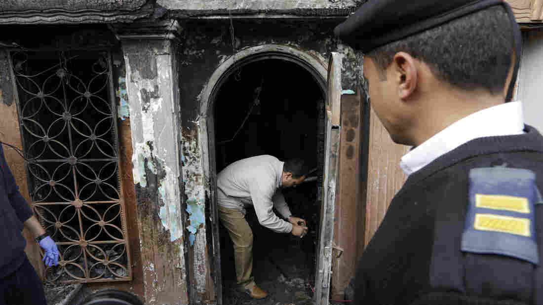 An Egyptian forensic expert checks the gate of the nightclub that was attacked in Cairo, Egypt, Friday. At least 16 people were killed in the attack.