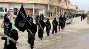 FILE - This undated file image posted on a militant website on Jan. 14, 2014, shows fighters from the Islamic State group marching in Raqqa, Syria. T (AP Photo/Militant Website, File)