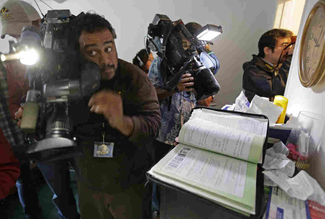 Members of the media crowd into the apartment bedroom of San Bernardino shooting suspects Syed Farook and his wife, Tashfeen Malik, in Redlands, Calif.