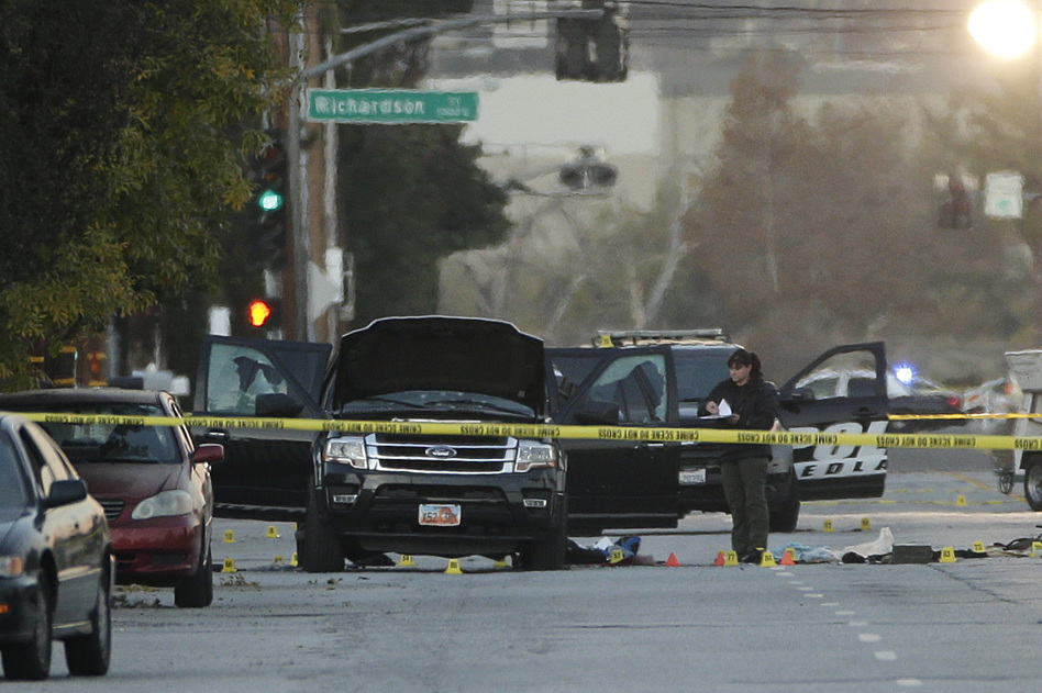 An investigator on Thursday looks at the SUV that was involved in a police shootout with suspects in San Bernardino, Calif. At least 14 people were killed Wednesday mornin (Jae C. Hong/AP)