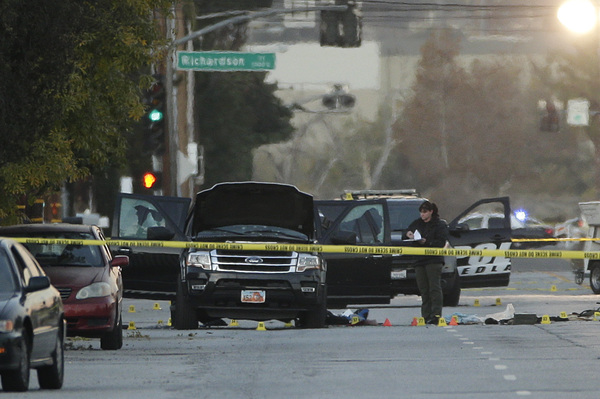 An investigator on Thursday looks at the SUV that was involved in a police shootout with suspects in San Bernardino, Calif. At least 14 people were killed Wednesday mornin