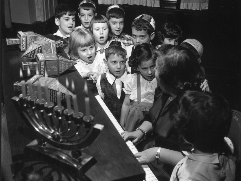 Young Jewish children gather around the piano, circa 1955, to perform songs during the Hanukkah celebrations.