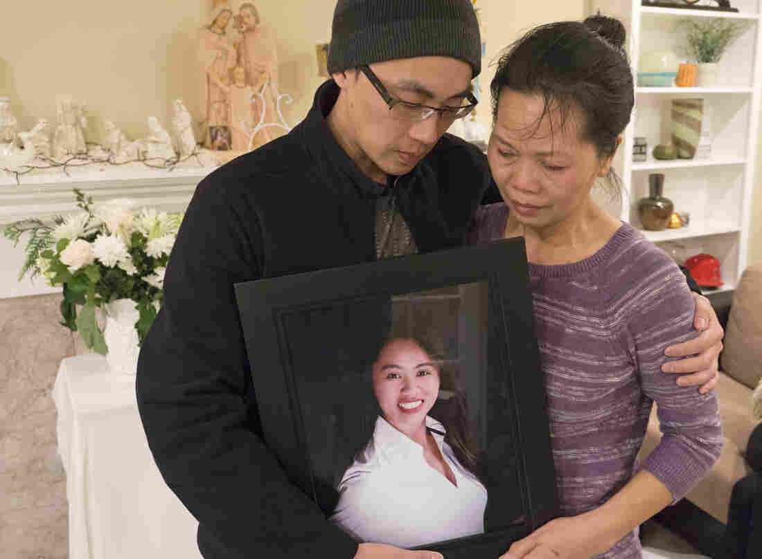 At their home in Santa Ana, Calif., Trung Do (left) and Vanessa Nguyen and hold a photograph of their sister and daughter Tin Nguyen, who died in the mass shooting.