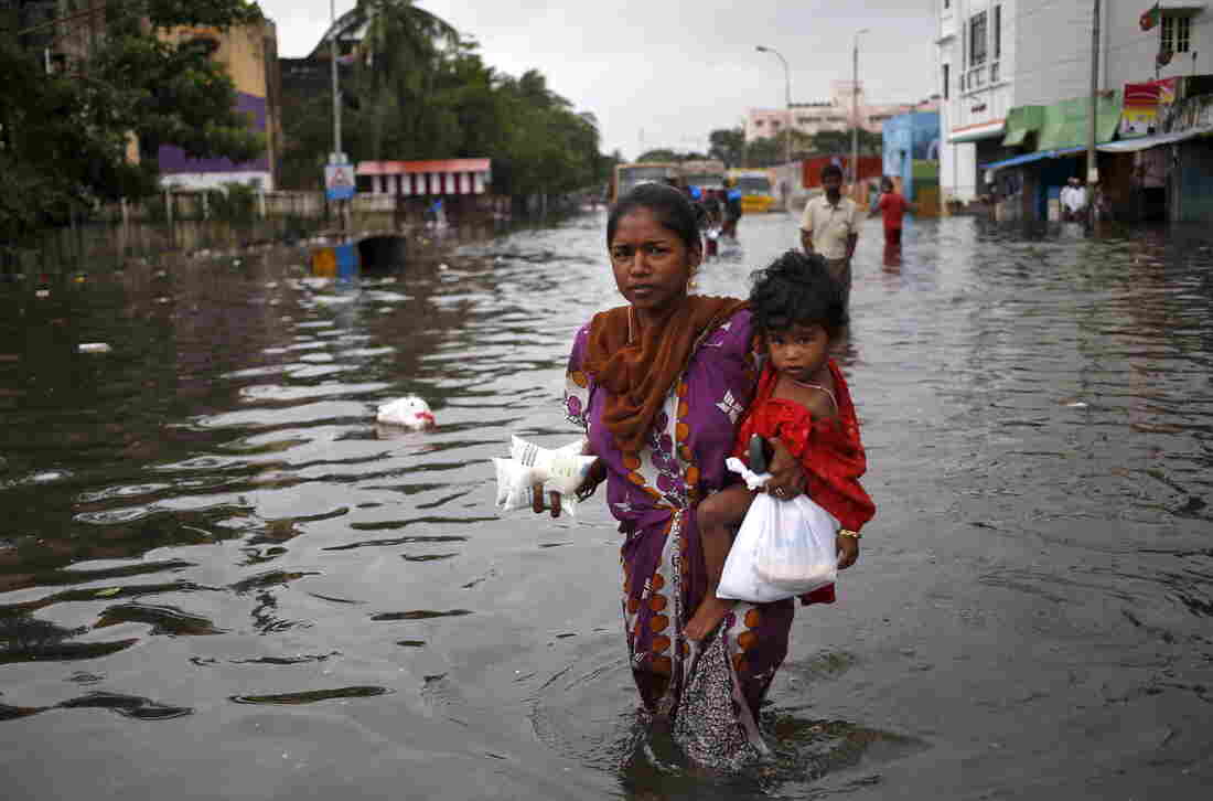 Child and milk packets in hand, a woman wades through a flooded street in Chennai on Saturday.