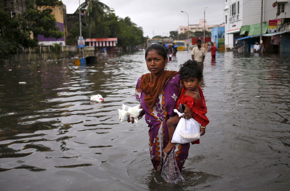 Child and milk packets in hand, a woman wades through a flooded street in Chennai on Saturday. (Anindito Mukherjee/Reuters/Landov)