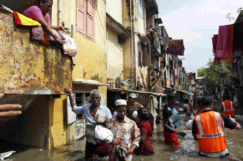Navy personnel distribute food packets to residents in flooded areas of Chennai on Friday.