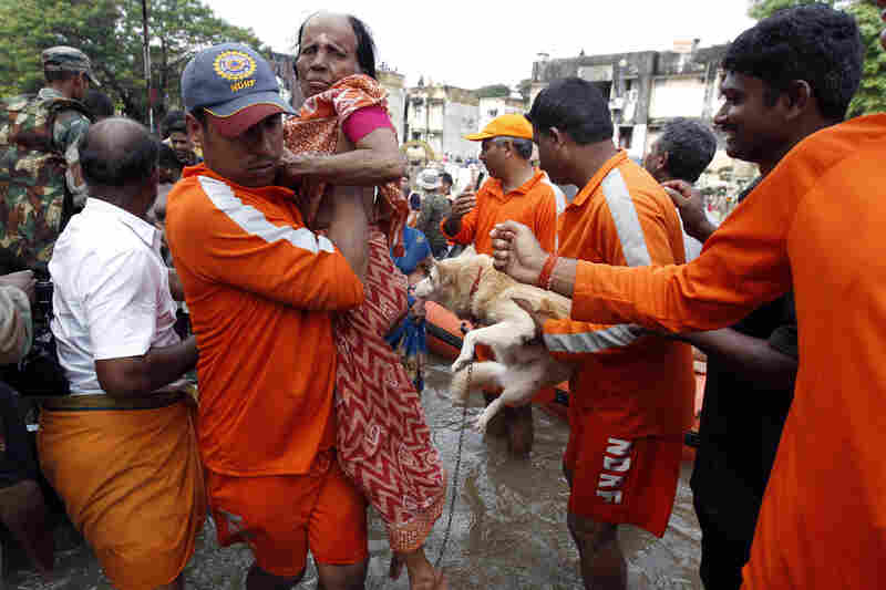 An elderly woman and a dog are carried from floodwaters by National Disaster Response Force personnel.