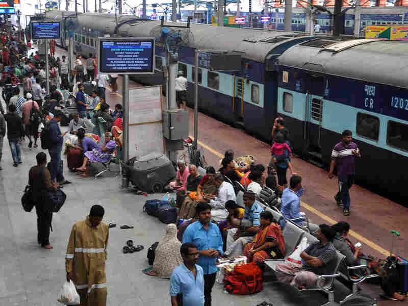 Commuters in Chennai wait at a railway station after most of the city's trains were suspended due to flooding.