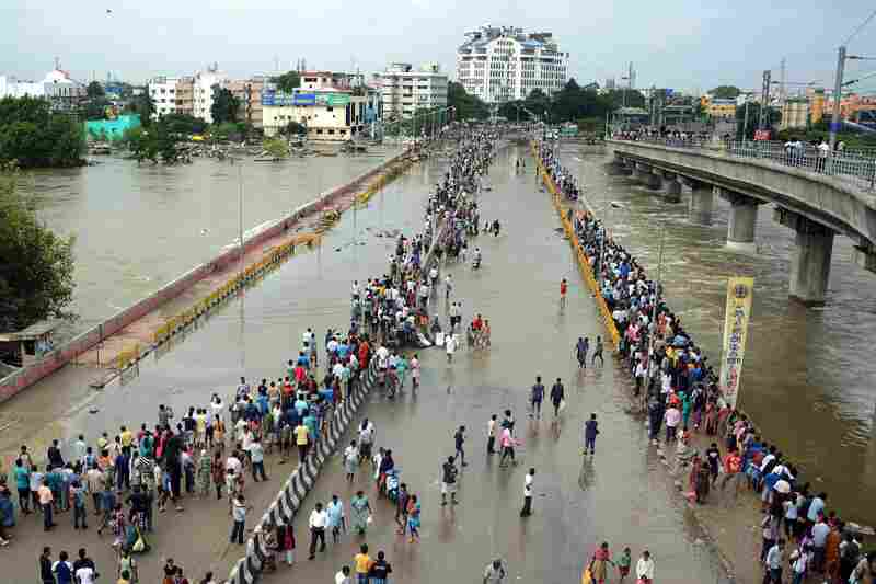 Indian residents attempt to cross a waterlogged highway in Chennai on Thursday.