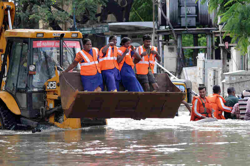 Rescue workers travel in the claw of a bulldozer as they work to rescue stranded residents on Thursday.