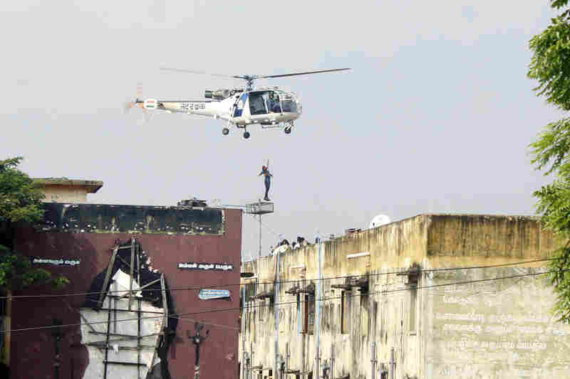 An Indian rescue helicopter lifts a man off an apartment roof on Friday.
