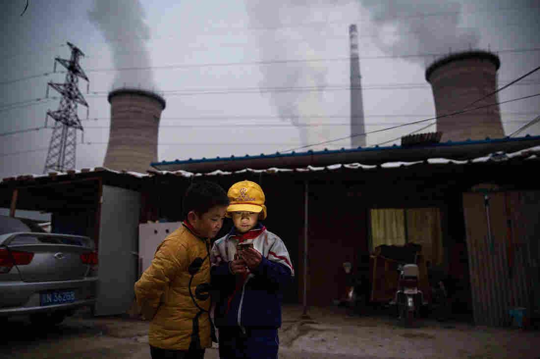 Young boys in Beijing check a smartphone in front of their home near a coal-fired power plant. As China's economy slowed in 2015, its industrial use of coal likely dropped, too, researchers say. That may be behind the slight drop in global CO2 emissions.