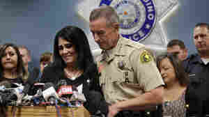 San Bernardino County Sheriff John McMahon comforts dispatcher Michelle Rodriguez during a news conference with the first responders who talked about their experiences in last week's terrorist attack.