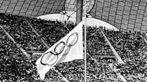 Olympic team members stand on the field as the Olympic flag flies at half-staff during a memorial service in the Munich Olympic Stadium in Germany on Sept. 6, 1972. Eleven Israeli team members were killed by Arab guerrillas at the Summer Olympic Games. A crowd of 80,000 filled the stadium to capacity.