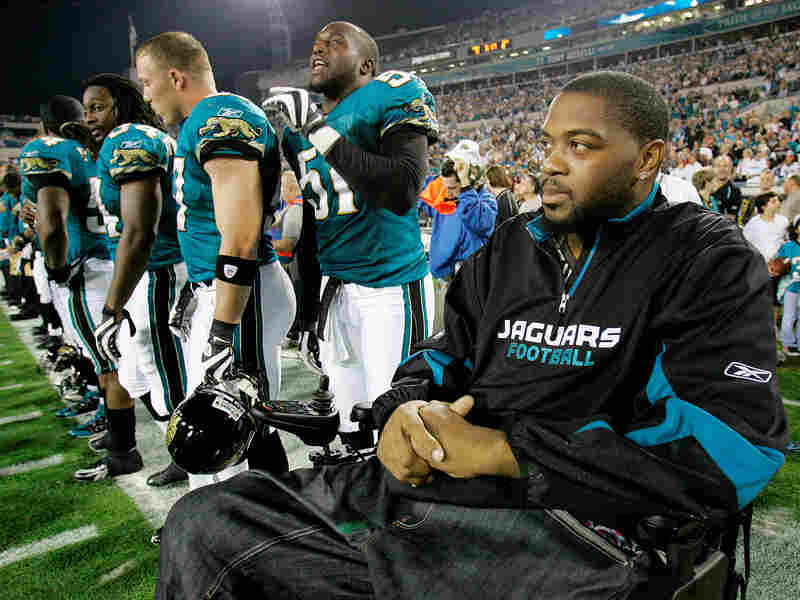 Jacksonville Jaguars player Richard Collier joins his teammates on the sidelines for the national anthem on Dec. 18, 2008.