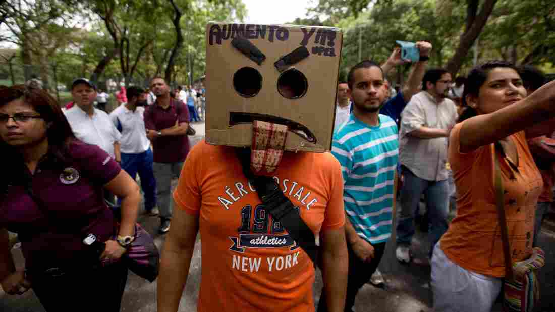"""A demonstrator wears a box that reads in Spanish, """"Salary raise now,"""" during a protest by university professors and students at Venezuela's Central University in Caracas on May 28. A typical professor's salary is now worth the equivalent of $35 a month due to runaway inflation. Leading public universities have been closed due to strikes since September."""