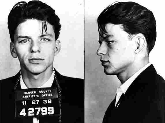 """Frank Sinatra poses for a mug shot after being arrested and charged with """"carrying on with a married woman""""."""