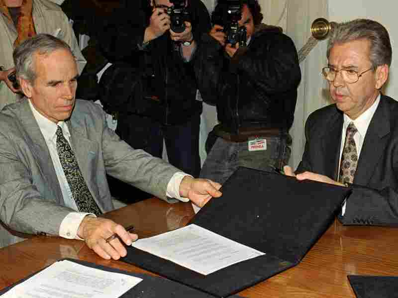 Douglas Tompkins (left) and Juan Villarzu, chief of staff of the Chilean president, with the text of a 1997 agreement permitting the development of a huge nature sanctuary in southern Chile.