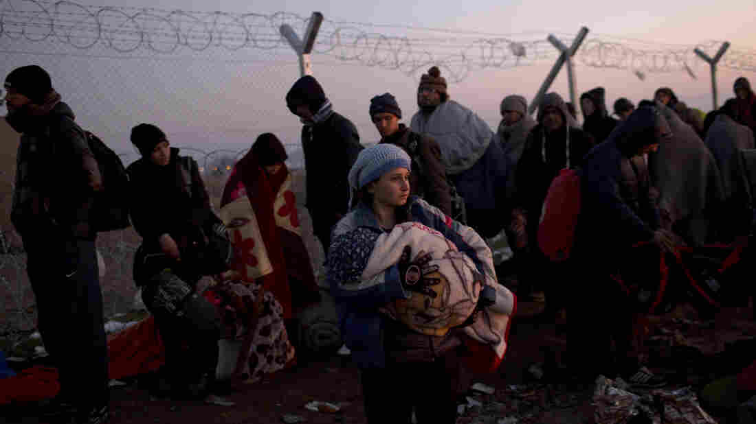 A woman holds her baby as she waits with other migrants on the Greek side of the fence along the border with Macedonia on Sunday. Macedonian is only allowing in refugees from the war-torn countries of Syria, Iraq and Afghanistan. Those not allowed into Macedonia are being bused to a sports stadium in Athens.