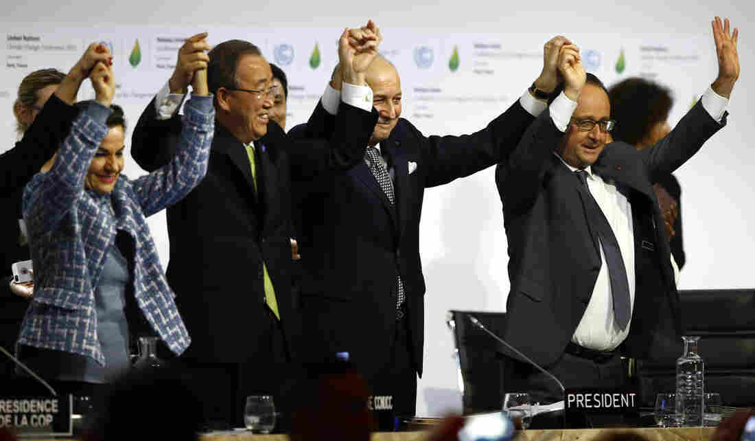 French President Francois Hollande, right, French Foreign Minister and president of the COP21 meetings Laurent Fabius, second right, UN climate chief Christiana Figueres, left, and UN Secretary-General Ban ki-Moon join hands after the final adoption of an agreement at the COP21 United Nations conference on climate change.