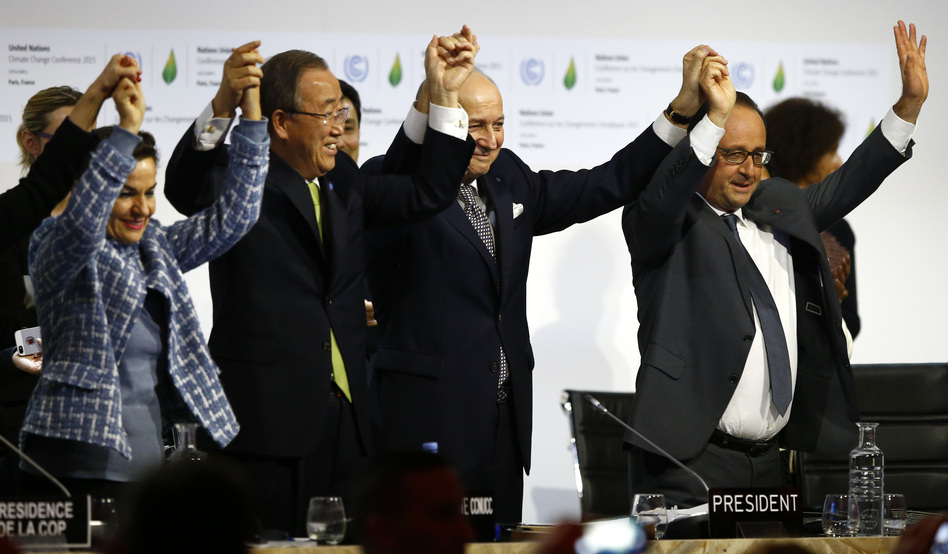 French President Francois Hollande, right, French Foreign Minister and president of the COP21 meetings Laurent Fabius, second right, UN climate chief Christiana Figueres, left, and UN Secretary-General Ban ki-Moon join hands after the final adoption of an agreement at the COP21 United Nations conference on climate change. (Francois Mori/AP)