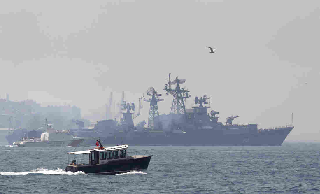 A Turkish boat (in the foreground) escorts the Russian naval destroyer Smetlivy, in the Bosphorus in Istanbul, in July 2012.