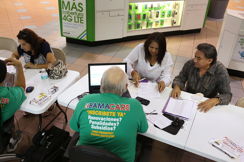 From left: Martha Lucia Bienvendida Barreno and Jorge Baquero discuss health insurance options with agents from Sunshine Life and Health Advisors at a Miami mall last month. (Joe Raedle/Getty Images)