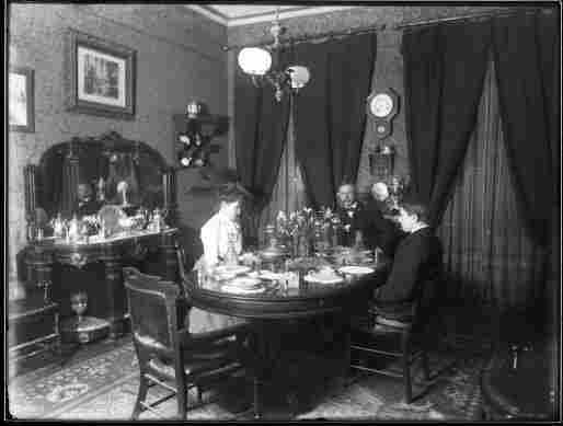A Victorian family sits at the table in their dining room.