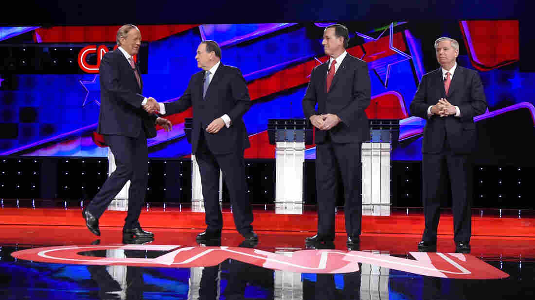 Republican presidential candidates (from left) George Pataki, Mike Huckabee, Rick Santorum and Lindsey Graham take the stage during Tuesday's undercard debate.