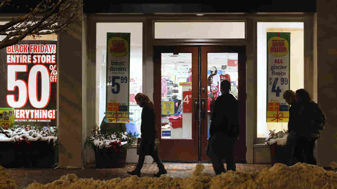 Shoppers in Freeport, Maine, pass by store windows advertising Black Friday deals after the stores opened their doors at midnight.