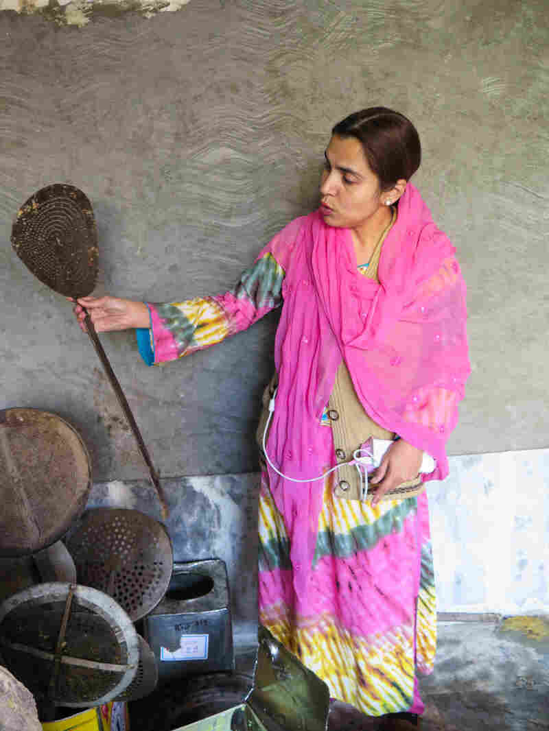 """""""You see the cleanliness of the utensils?"""" Ayesha Mumtaz asks scathingly, as she holds up a giant spoon crusted with filth during a raid on a backyard sweets factory in Lahore, Pakistan."""
