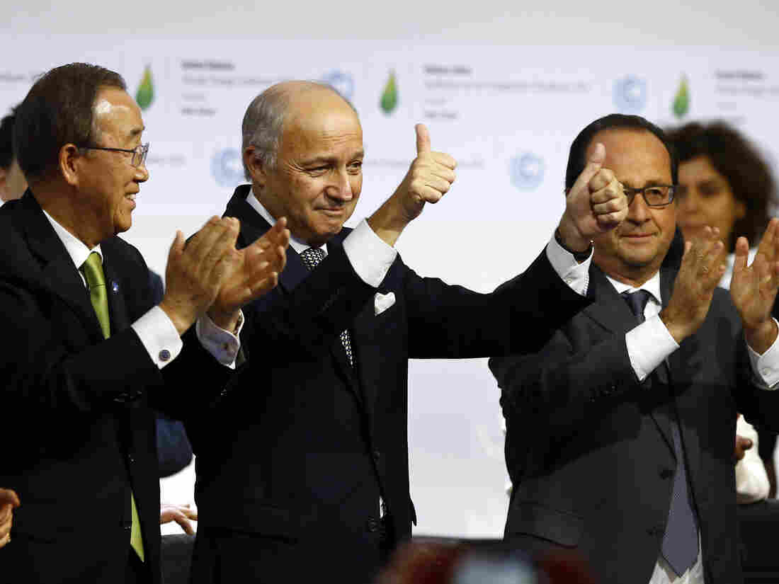 French Foreign Minister and President of the COP21 Laurent Fabius (center) gives a thumbs up while U.N. Secretary-General Ban Ki-moon (left) and French President Francois Hollande applaud after the final meeting of the U.N. conference on climate change in Le Bourget, France, on Saturday.