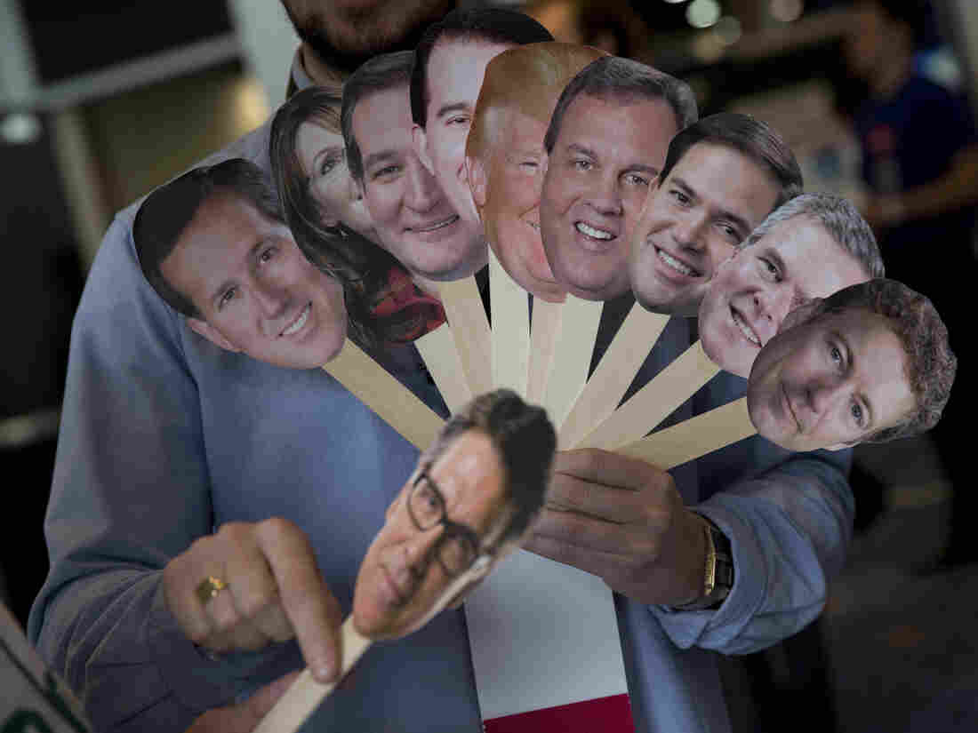 A reporter holds images of possible Republican candidates back in February. Since then, the GOP field has narrowed slightly, but still boasts 14 contenders.