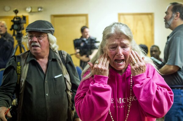 A Flint resident cries out during the filing of a class action lawsuit against city and state government officials on Monday, Nov. 16, 2015.