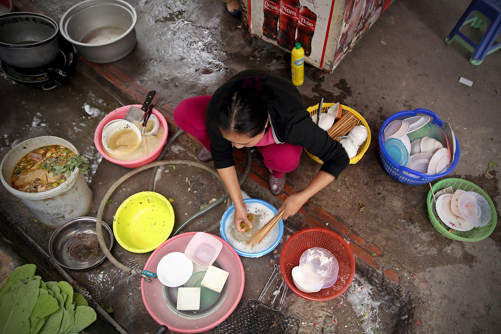 A woman washes dishes on the street in Hanoi, Vietnam. The World Health Organization says the burden of foodborne disease in Southeast Asia is one of the highest in the world.