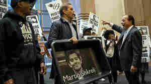 A file photo shows AIDS activists carrying an image of Turing Pharmaceuticals CEO Martin Shkreli in a makeshift cat litter pan, angry over his company's move to raise a drug's cost. Shkreli was arrested on charges unrelated to that 5,000 percent price hike.