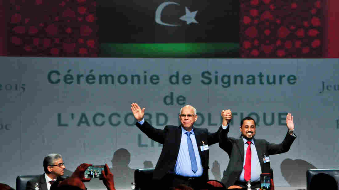 Delegates from the Libyan political dialogue participants raise their hands at the signing ceremony of the Libyan Political Agreement in Skhirat, Morocco, on Friday.