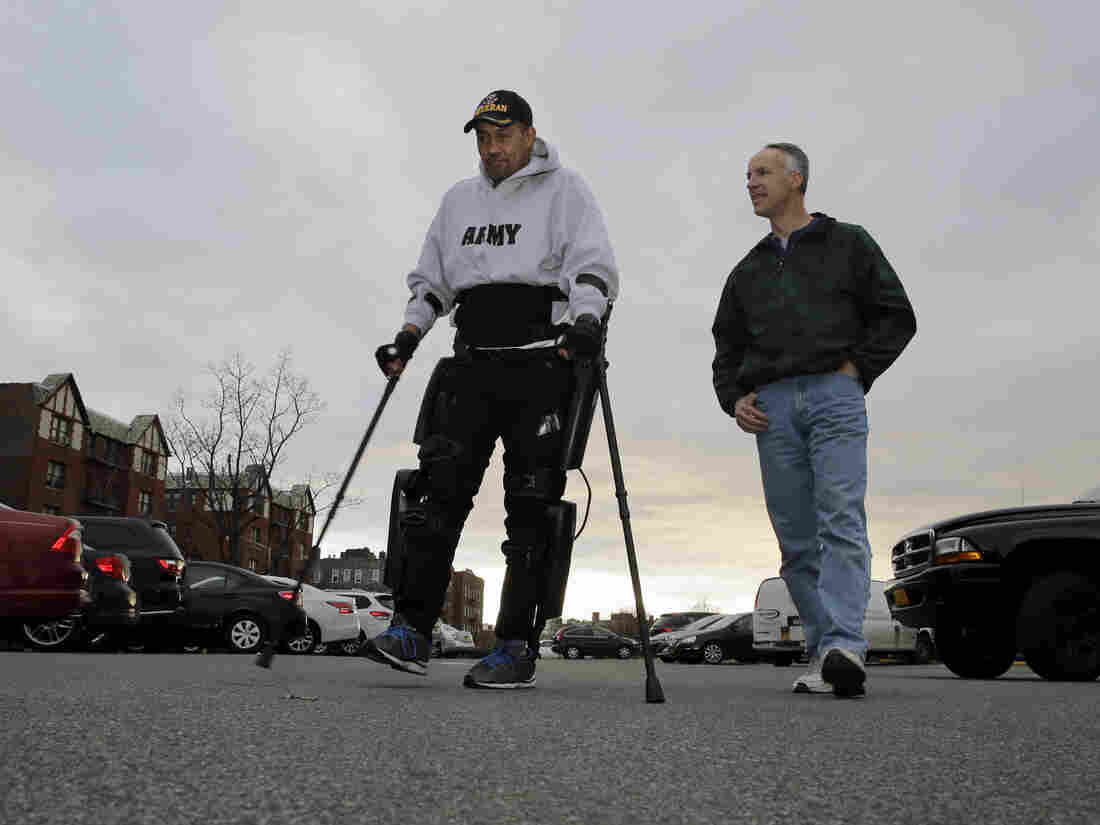 ReWalk Robotics service engineer Tom Coulter (right) looks on as paralyzed Army veteran Gene Laureano walks using a ReWalk device on Wednesday in the Bronx, N.Y.