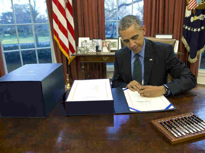 President Obama signs the budget bill in the Oval Office on Friday.