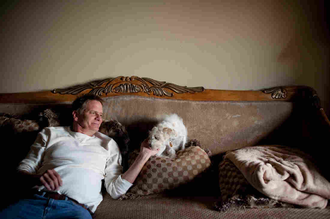 "Schiller spends time with his Yorkie-doodle, Maxine, at his apartment. As a result of his mounting medical bills and his inability to work, he says he is now ""next to poverty."""