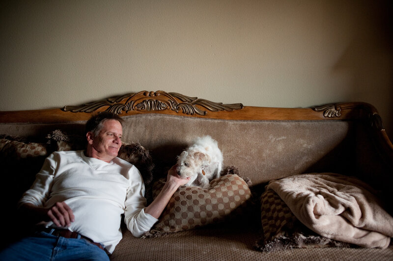 "Schiller spends time with his Yorkie-doodle, Maxine, at his apartment. As a result of his mounting medical bills and his inability to work, he says he's now ""next to poverty."" (Brandon Thibodeaux for NPR)"