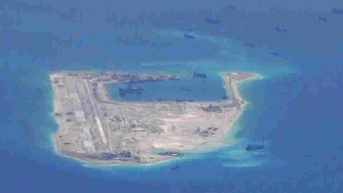 Chinese dredging vessels are purportedly seen in the waters around a reef in the disputed Spratly Islands, in a still image from video taken by a U.S. Navy surveillance aircraft in May. China says a U.S. bomber got too close to one of the islands.