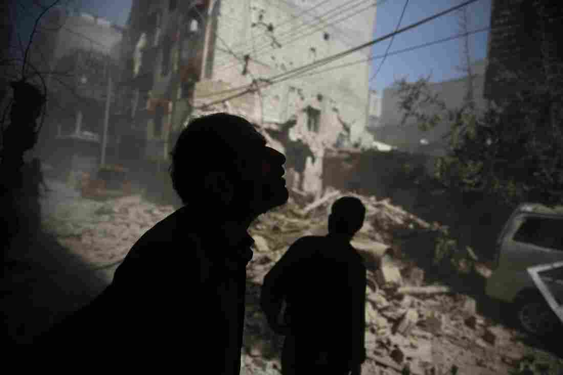 Syrians look at the damage following air strikes on the rebel-held area of Douma, east of the capital Damascus in October 2015.